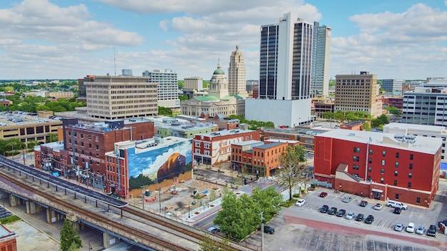インディアナ州フォートウェイン(米国)のダウンタウンの街並みの画像と線路とバイソンの壁画