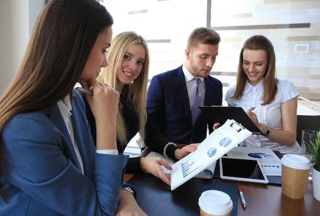 Изображение четырех успешных женщин-предпринимателей, смотрящих в камеру на встрече