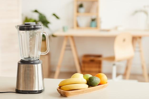 キッチンのテーブルの上に立っているブレンダーでカクテルのために準備された新鮮な果物の画像
