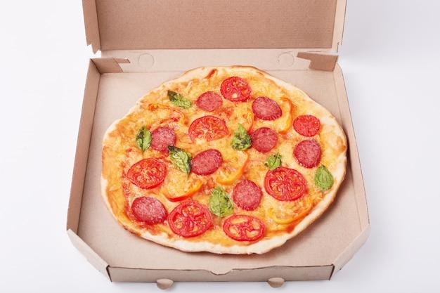 白い表面の段ボール箱に新鮮なおいしいピザのイメージ、ファーストフード料理の写真、レストランやカフェからの夕食
