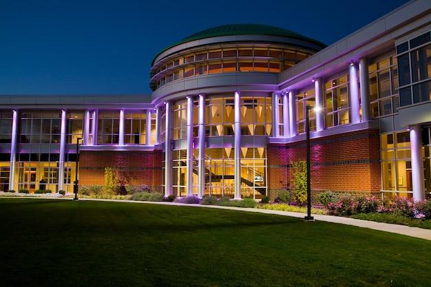 夕暮れ時に多くの窓があるモダンな建物の正面玄関の画像が紫色に点灯