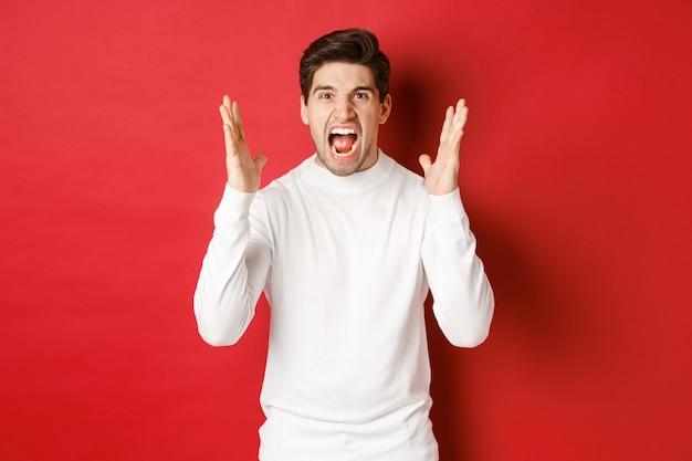 Изображение расстроенного и злого человека в белом свитере, кричащего от ярости, злящегося на кого-то, стоящего ...