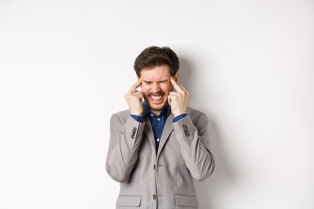 Изображение разочарованного человека, который пытается думать, не может что-то вспомнить, касается висков и щурится с напряженной гримасой, мозговой штурм, поиск решения, белый фон.