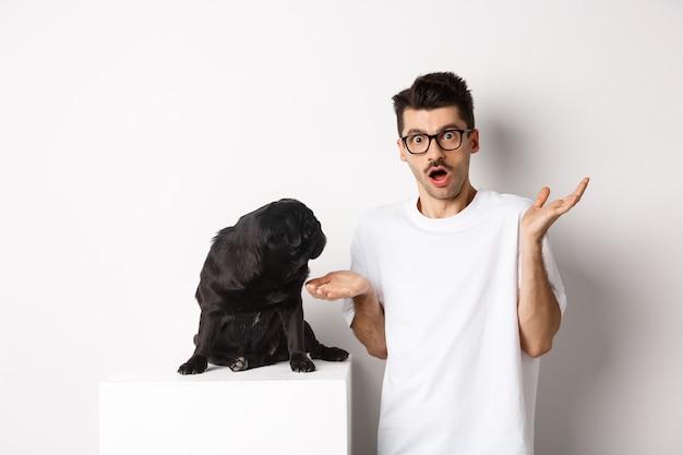 Изображение смешного черного мопса, смотрящего на своего растерянного хозяина, человека, озадаченного пожимающим плечами, стоящего на белом фоне