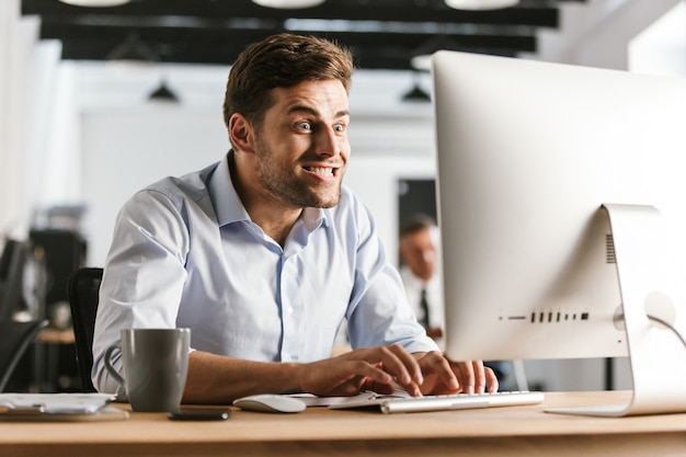 オフィスのテーブルのそばに座ってコンピューターを使用して面白いビジネスマンの画像