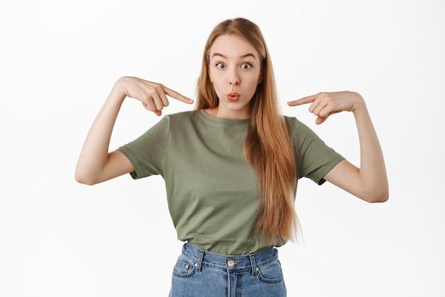 소녀의 이미지는 자신을 가리키고 갑자기 선택되거나 선택되어 캐주얼 옷을 입고 흰 벽 위에 서 있는 것처럼 놀라고 놀란 것처럼 보입니다.