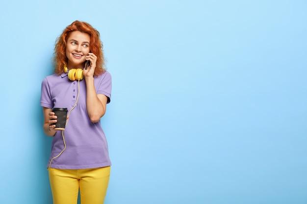 Изображение радостной молодой девушки-модели устраивает аранжировки через смартфон