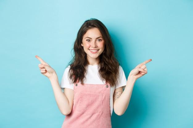 明るいメイク、横向きの指、笑顔の魅力的な美しい少女の画像。プロモーションオファーの2つのバリエーションを示し、選択肢を提供し、青い背景を表示します。