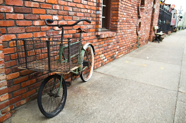 루이빌의 붉은 벽돌 건물 옆 보도에 검은 바구니가 달린 녹색 자전거 이미지