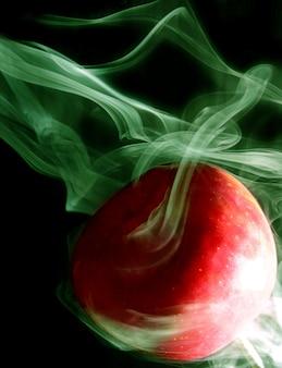 녹색 연기의 이미지는 검정색 배경에 둥근 빨간 사과를 감싸고 있습니다.
