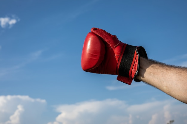 青い曇り空の上に赤いボクシンググローブを身に着けている手と戦う準備ができているハンドボクシンググローブの画像