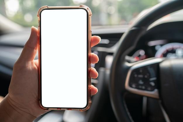 차에 흰색 화면으로 휴대 전화를 들고 손의 이미지.
