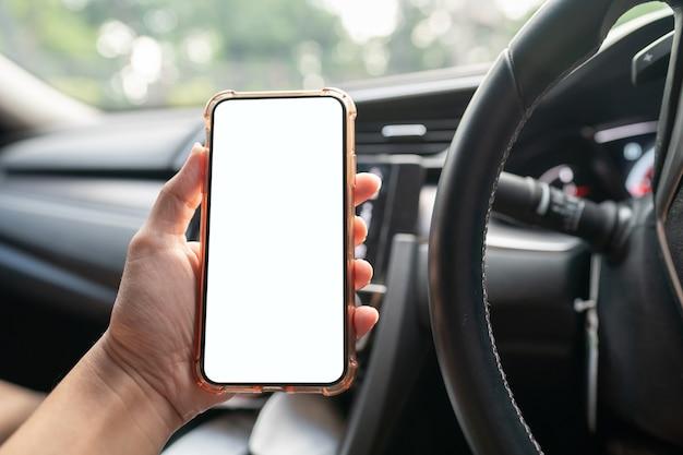 車の中で白い画面で携帯電話を持っている手の画像。