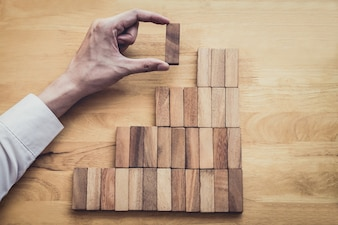 Image of hand of business placing and pulling wood block to complete in game