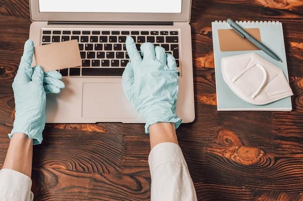 노트북의 배경에 의료 장갑에 손의 이미지. 여자는 플라스틱 은행 카드를 들고 웹사이트에 번호를 입력합니다. 온라인 쇼핑 개념입니다. 검역 중 보안