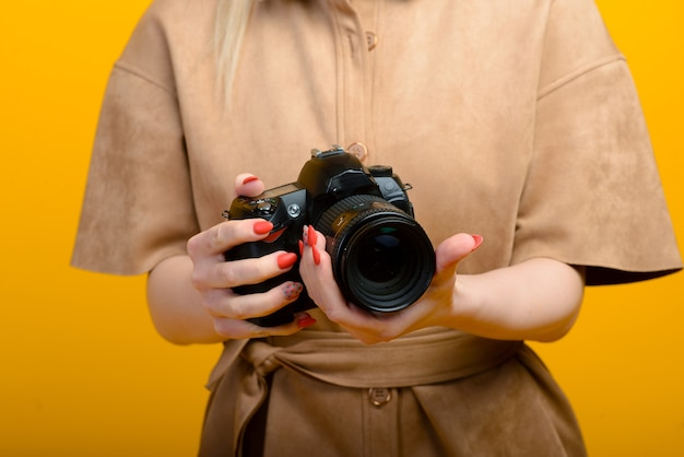빈 노란색 배경에 디지털 사진 카메라로 손의 이미지