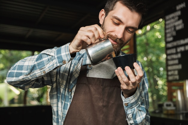 屋外のカフェや喫茶店で働いているときにコーヒーを作るエプロンを着ているハンサムなバリスタ男の画像