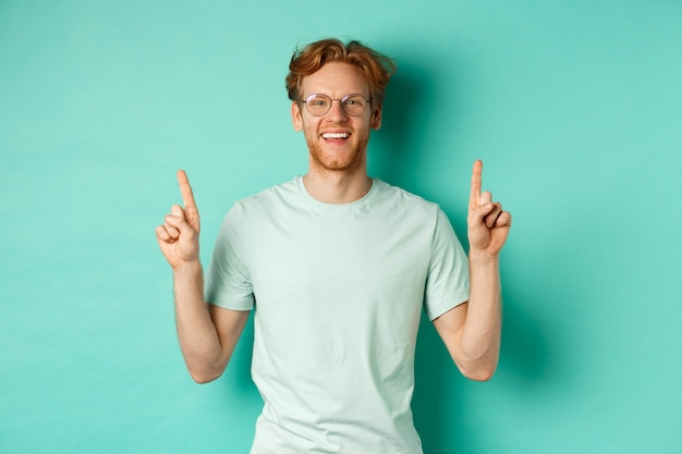 赤い髪のハンサムなひげを生やした男の画像、tシャツと眼鏡をかけて、幸せそうに笑って、指を上に向けて、プロモーションのオファーを示し、ターコイズブルーの背景の上に立っています。