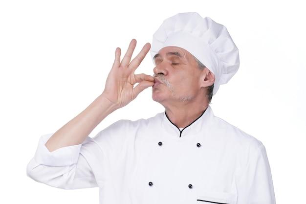 Изображение красивого бородатого шеф-повара старшего мужчины в помещении, изолированном над белой стеной