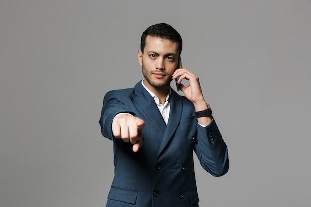 Изображение красивого делового человека, говорящего по мобильному телефону, позирует изолированным над серой стеной, указывая на вас.
