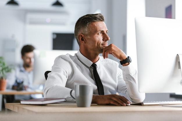 白いシャツとネクタイを着て、コンピューターでオフィスの机に座って、脇を見て30代のハンサムなビジネスマンの画像
