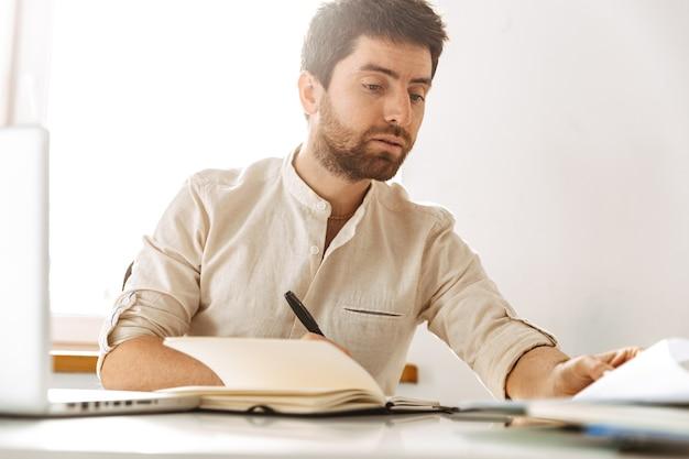 Изображение красивого бизнесмена 30-х годов в белой рубашке, работающего с ноутбуком и бумажными документами, сидя в ярком офисе