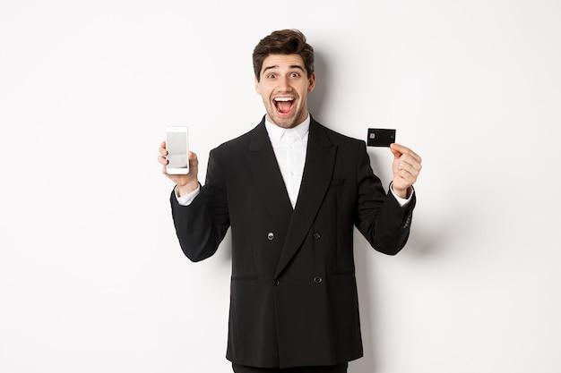 興奮しているように見え、白い背景に立って、携帯電話の画面でクレジットカードを表示している黒いスーツを着たハンサムなビジネスマンの画像