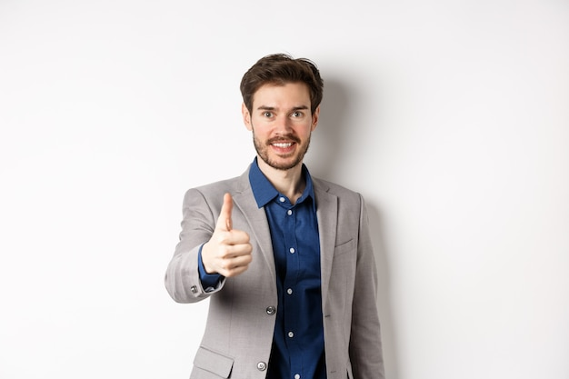 Изображение красивого бизнесмена в костюме показывая большой палец руки вверх и усмехаясь, стоя на белой предпосылке.