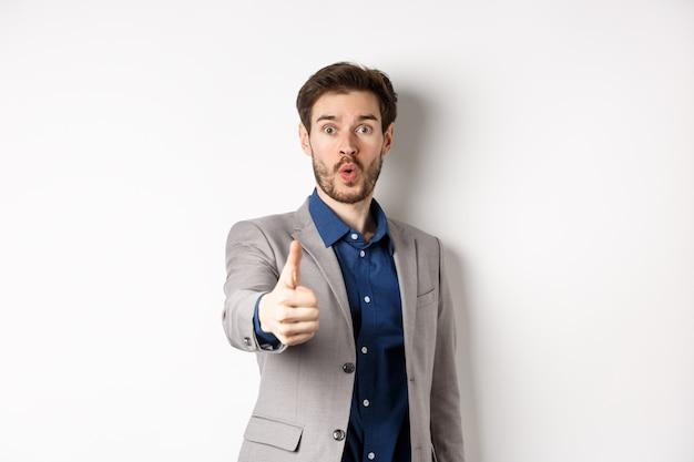Изображение красивого бизнесмена в костюме показывая большой палец руки вверх с возбужденным лицом, стоя на белой предпосылке.