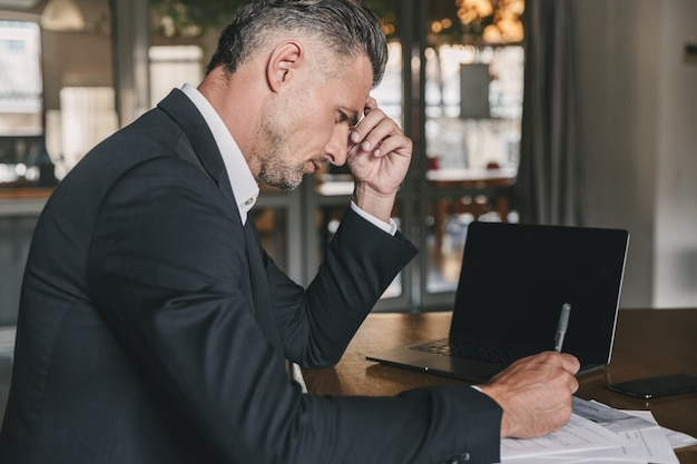 문서와 노트북으로 작업하는 동안 사무실에서 테이블에 앉아 흰 셔츠와 검은 양복을 입고 잘 생긴 백인 사업가의 이미지