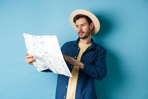 旅行マップを見て、夏休み中にルートを勉強し、青い背景に麦わら帽子に立っているハンサムな白人男性の画像。