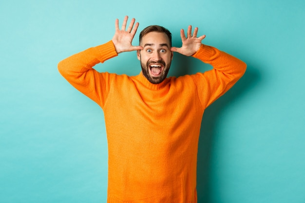 재미 있은 얼굴을 만들고, 누군가를 조롱하고 웃고, 가벼운 청록색 벽에 서있는 잘 생긴 백인 남자의 이미지.