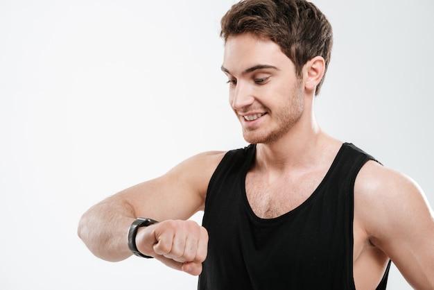 時計を見て白い壁の上に立っている黒いtシャツを着たハンサムな陽気な若い男の画像。