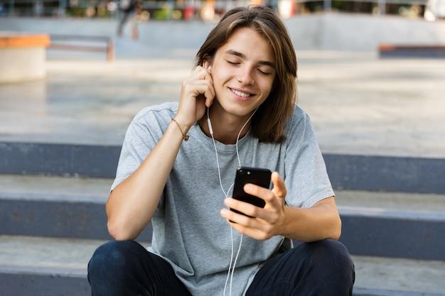 ハンサムな陽気な若いスケーターの男の画像は、電話を使用してイヤホンで音楽を聴いて公園に座っています。