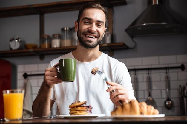 Изображение красивого парня 30-х, сидящего за столом и завтракающего в современной квартире