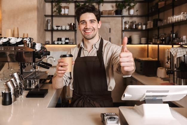엄지손가락을 보여주는 커피 컵을 들고 실내에서 일하는 카페 바에서 포즈를 취하는 잘생긴 행복한 커피 남자의 이미지.