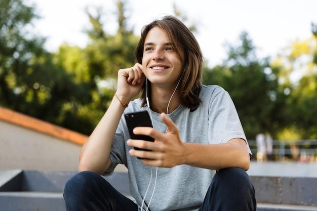 ハンサムな幸せな若いスケーターの男の画像は、電話を使用してイヤホンで音楽を聴いて公園に座っています。