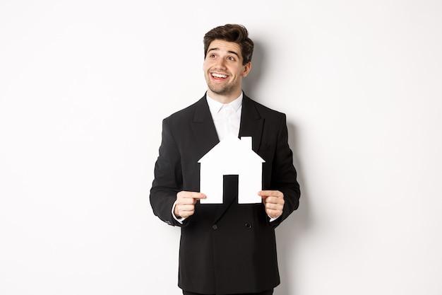 黒のスーツを着たハンサムな投資家の画像、ハウスメイクを保持し、白い背景に立って、思慮深く左上隅を見て
