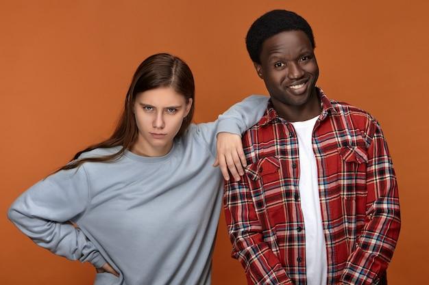 格子縞のシャツを着て広く笑っているハンサムな楽しい若い黒人男性の画像、感情的な深刻なガールフレンドが彼の肩に肘を保ちながら白いまっすぐな歯を示しています