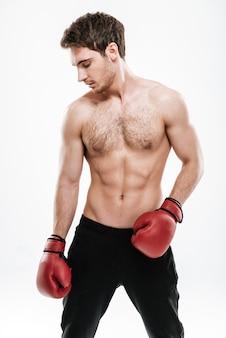 Изображение боксера красивого человека, стоящего над белой стеной. посмотри в сторону.