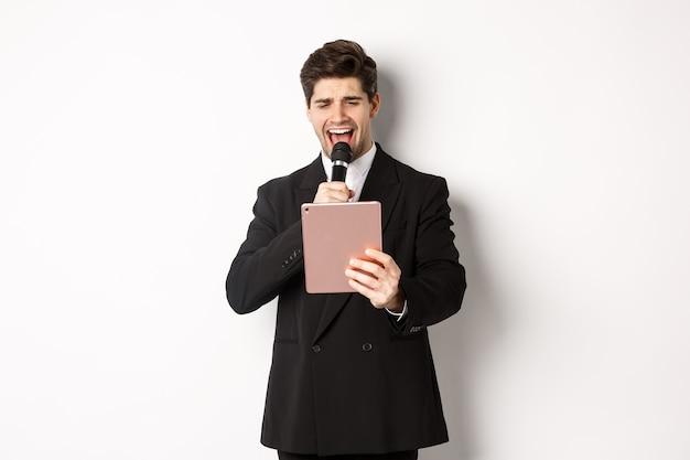 黒のスーツを着て、デジタルタブレットでカラオケを歌い、マイクを持って、白い背景の上に立っているハンサムな男の画像。