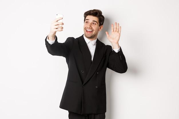 スーツを着たハンサムな男性の画像。ビデオ通話をしてスマートフォンのカメラに手を振って、ビデオを録画し、誰かに挨拶し、白い背景に立っています。