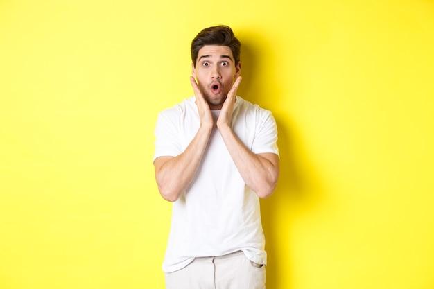 黄色の背景の上に立って、驚いて、あえぎ、すごいことを言って、プロモーションオファーを見て驚いているハンサムな男の画像
