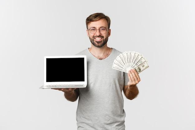 Изображение красивого мужчины с бородой, работающего с ноутбуком