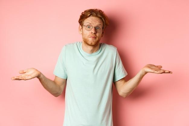 Изображение красивого рыжего мужчины в очках и футболке ничего не знающего, пожимающего плечами и растерянно приподнимающего брови, ничего не понимающего на розовом фоне.