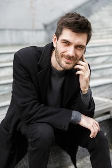 Изображение красивого молодого бизнесмена, сидящего на открытом воздухе, разговаривает по мобильному телефону.