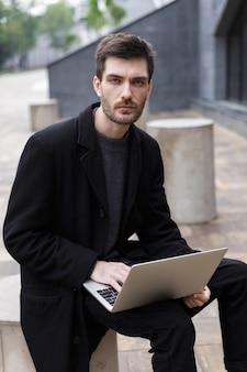 노트북 컴퓨터를 사용 하여 야외에서 앉아 잘 생긴 젊은 사업가의 이미지.