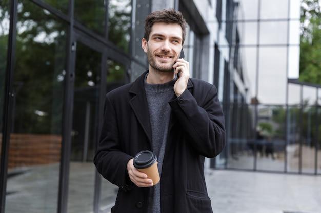 야외에서 커피를 마시는 전화로 얘기 산책 잘 생긴 젊은 사업가의 이미지.