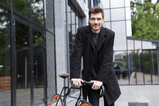 자전거와 함께 야외에서 걷는 잘 생긴 젊은 사업가의 이미지.