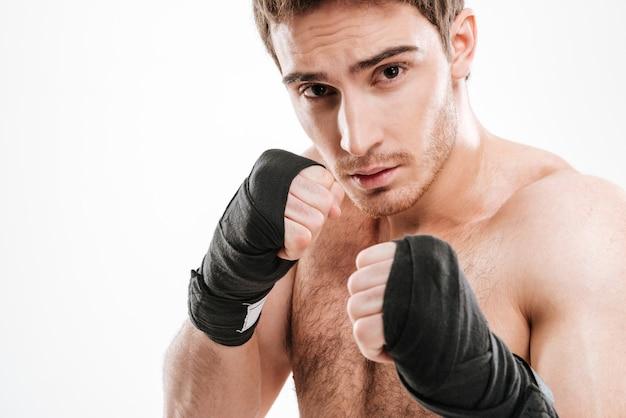 Изображение красивого боксера молодого человека, стоящего над белой стеной.